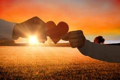 Image composée des couples tenant le papier de papier de forme de coeur Photo libre de droits
