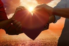 Image composée des couples tenant un coeur Photographie stock