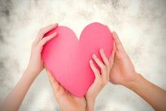Image composée des couples tenant un coeur de papier Photographie stock