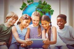 Image composée des enfants à l'aide du comprimé numérique au parc Photo libre de droits