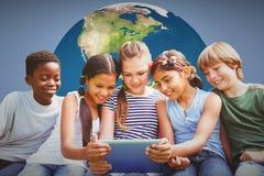 Image composée des enfants à l'aide du comprimé numérique au parc Image stock