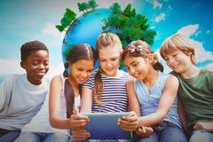 Image composée des enfants à l'aide du comprimé numérique au parc Photo stock