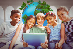Image composée des enfants heureux à l'aide du comprimé numérique au parc Photo stock