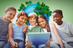 Image composée des enfants heureux à l'aide du comprimé numérique au parc Images stock