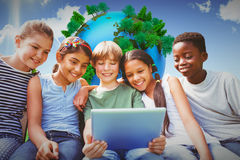 Image composée des enfants heureux à l'aide du comprimé numérique au parc Photo libre de droits