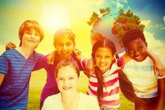 Image composée des enfants heureux formant le petit groupe au parc Images stock