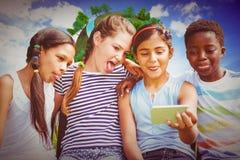 Image composée des enfants heureux prenant le selfie au parc Images libres de droits