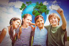 Image composée des enfants heureux prenant le selfie au parc Photos stock