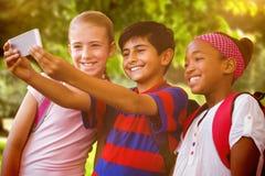 Image composée des enfants heureux prenant le selfie dans le couloir d'école Image libre de droits