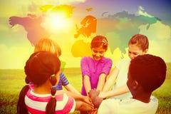 Image composée des enfants tenant des mains ensemble au parc Photos stock