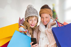 Image composée des femmes de sourire avec des paniers regardant le téléphone portable Photo stock