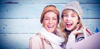 Image composée des femmes de sourire regardant l'appareil-photo avec des paniers Photographie stock
