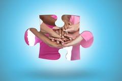 Image composée des femmes heureuses portant des rubans de cancer du sein avec des mains ensemble photos libres de droits