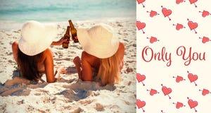 Image composée des filles buvant sur des mots de plage et de valentines Images stock