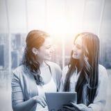 Image composée des filles de sourire tenant le comprimé Photographie stock libre de droits
