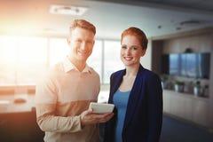 Image composée des gens d'affaires de sourire à l'aide d'un comprimé numérique Image libre de droits