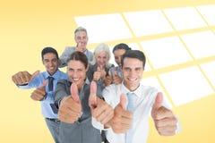 Image composée des gens d'affaires heureux regardant l'appareil-photo avec des pouces  Photos stock