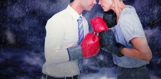 Image composée des gens d'affaires portant et enfermant dans une boîte les gants rouges images libres de droits