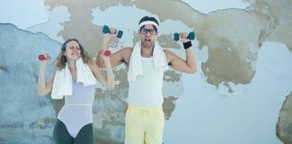 Image composée des haltères de levage de couples geeky de hippie dans les vêtements de sport Photos libres de droits