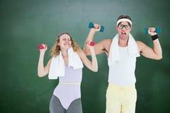 Image composée des haltères de levage de couples geeky de hippie dans les vêtements de sport Image libre de droits