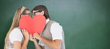 Image composée des hippies geeky embrassant derrière la carte de coeur Images stock