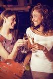 Image composée des jeunes femmes gaies grillant des cannelures de champagne au compteur de barre Images libres de droits