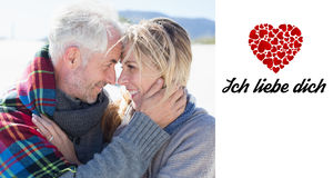 Image composée des ménages mariés heureux embrassant sur la plage Photographie stock