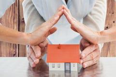 Image composée des mains de couples avec la maison modèle Photo stock