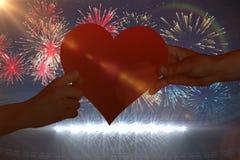Image composée des mains tenant le coeur rouge Image libre de droits