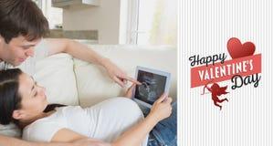 Image composée des parents éventuels regardant le balayage d'ultrason sur le PC de comprimé Image stock