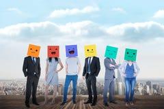 Image composée des personnes avec des boîtes sur leurs têtes Image stock