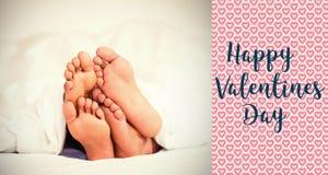 Image composée des pieds de couples dans des mots de lit et de valentines Photographie stock libre de droits
