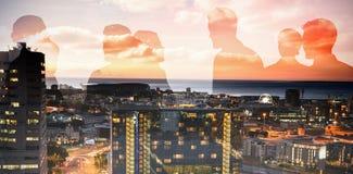 Image composée des silhouettes se serrant la main images stock