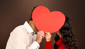 Image composée des visages de bâche de couples avec le coeur de papier Photographie stock libre de droits