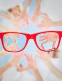 Image composée des volontaires avec des mains ensemble contre le ciel bleu Image stock