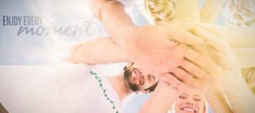 Image composée des volontaires heureux avec des mains ensemble contre le ciel bleu Photographie stock libre de droits