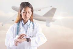 Image composée du docteur asiatique à l'aide de sa montre intelligente Photos stock