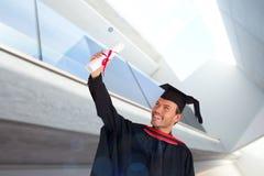 Image composée du garçon attirant heureux célébrant son obtention du diplôme Image stock