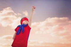 Image composée du garçon masqué feignant pour être super héros sur l'écran blanc Photos libres de droits
