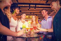 Image composée du groupe d'amis agissant l'un sur l'autre les uns avec les autres tout en ayant le cocktail Image libre de droits