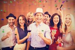 Image composée du groupe d'amis ayant l'amusement tout en se tenant avec des boissons Photo libre de droits