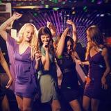 Image composée du groupe d'amis de sourire dansant sur la piste de danse Photographie stock libre de droits