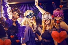 Image composée du groupe d'amis de sourire dansant sur la piste de danse Image stock