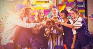Image composée du groupe d'amis grillant le verre de bière en partie Image stock