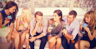 Image composée du groupe d'amis parlant et ayant des boissons Photos stock