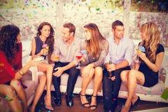 Image composée du groupe d'amis parlant et ayant des boissons Photographie stock