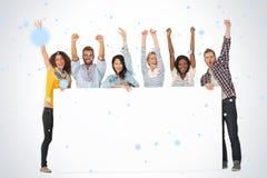 Image composée du groupe de sourire de jeunes amis montrant la grande affiche et encourager Photographie stock libre de droits