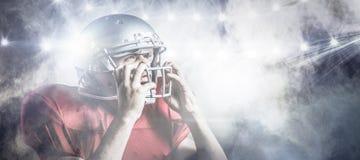 Image composée du joueur de football américain agressif tenant le casque Photographie stock libre de droits