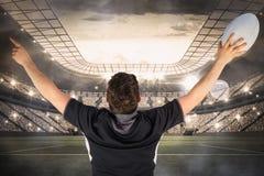 Image composée du joueur de retour tourné de rugby faisant des gestes la victoire Photos stock