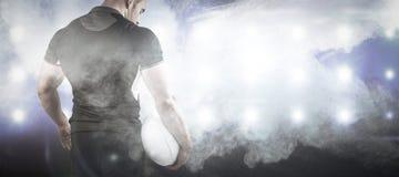Image composée du joueur dur de rugby tenant la boule Image stock